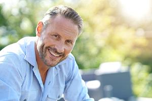 Older man with dental implants in Edmonton, AB sitting outside smiling